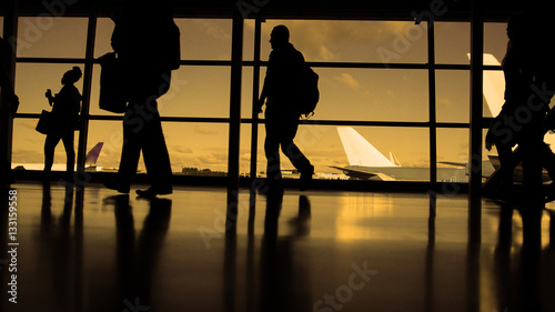 In de dag Luchthaven Travellers with suitcases and baggage in airport walking to departures in front of window, silhouette, warm