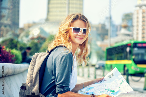 obraz PCV happy young woman with a city map and a backpack smiling