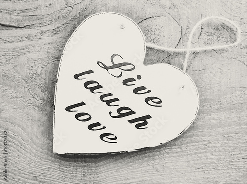 Photo  Decorative white wooden heart with the slogan live laugh love on grey wooden background