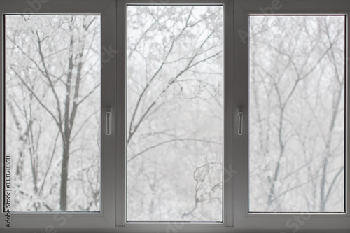 Window with winter view of snowy background. Wallpaper Mural