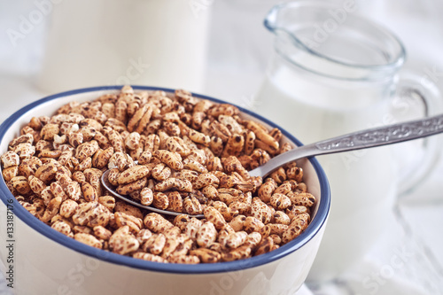 Fotografia, Obraz  Puffed barley cereal in bowl with pitcher of milk in background