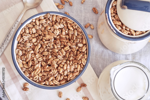 Valokuva  Puffed barley cereal in bowl with pitcher of milk. Top view