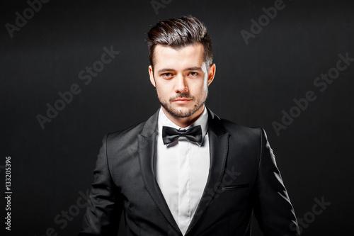 portrait of confident handsome man in black suit with bowtie posing in dark stud Fototapeta
