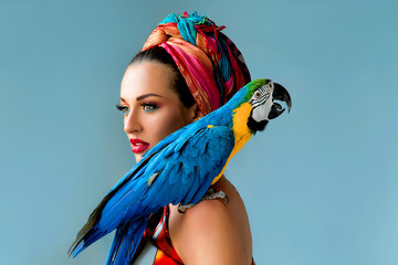 Portrait of young attractive woman in african style with ara parrot on her showlder on colorful background