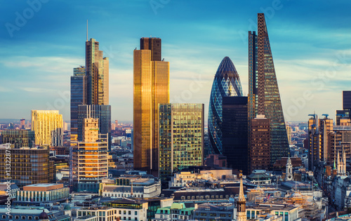 Photo Stands London The bank district of central London with famous skyscrapers and other landmarks at sunset with blue sky - London, UK