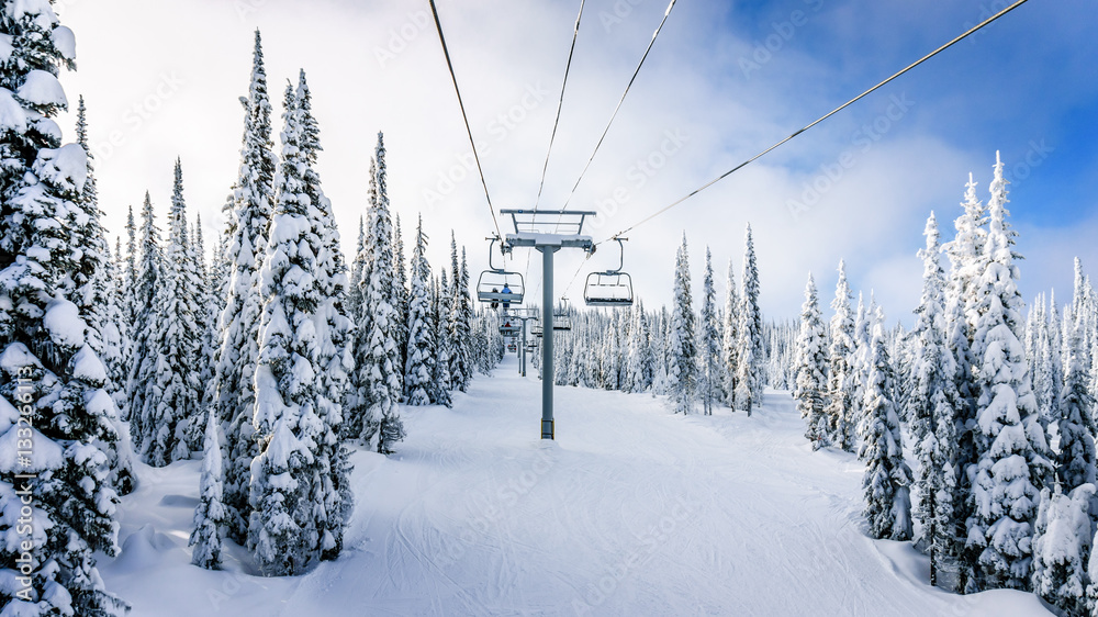 Fototapety, obrazy: Riding the Chair Lift in a Winter Landscape on the Ski Hills near Sun Peaks village in the Shuswap Highlands of central British Columbia, Canada