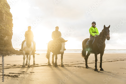 Foto auf AluDibond Reiten People with horses on the beach on a cloudy day