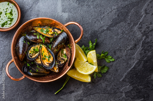 Photo  Mussels in copper bowl, lemon, herbs sauce and white wine.