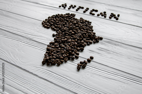 Wall Murals Coffee beans Map of the Africa made of roasted coffee beans laying on white wooden textured background and space for text
