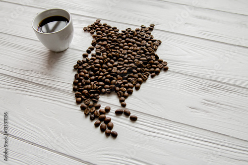 Wall Murals Coffee beans Map of theNorthern America made of roasted coffee beans laying on white wooden textured background with cup of coffee and space for text