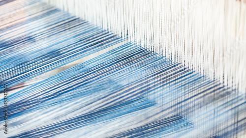 Fotografiet  Closeup, abstract motion blur of silk fabric weaving
