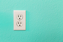 Electrical Sockets In Colorful Bright Teal Wall Of House.