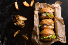 Three Burgers On A Dark Wooden Table