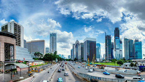 Panorama of beautiful skyline of Jakarta, Indonesia. Showing modern skyscraper buildings and beautiful blue sky and white cloud at daylight and big road with moderate traffic. Captured in Jend. Sudirm