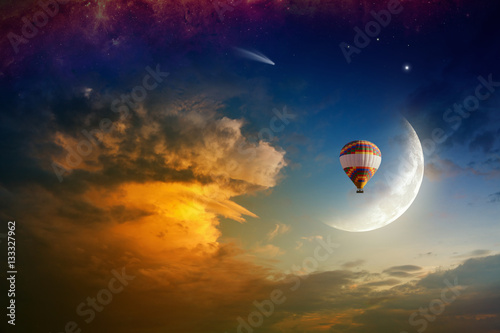 Dream concept - hot air balloon in glowing sky with rising moon