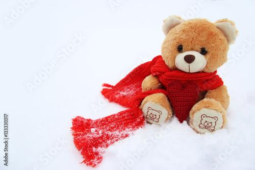 Игрушечный мишка на снегу с вязанным сердцем #133330317