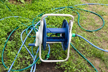 Tangled Garden Hose With A Reel On Grass