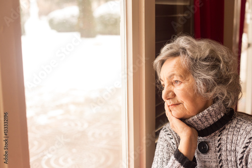 Fotografie, Obraz  Senior woman looking through window