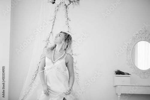 Foto op Canvas womenART Curly blonde girl in a white silk gown boudoir robe on bed.