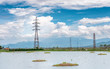 Transmission tower, electricity pylon or a power pylon, standing majestically lined up to the horizon, in front of large lake or pond, also with beautiful cloud and mountain in the background,