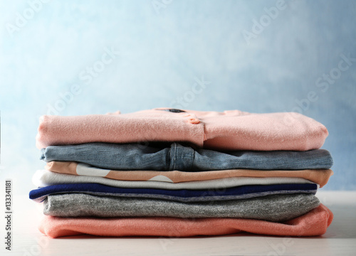 Photographie Stack of colorful clothes on light background