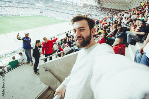 Photo  Handsome bearded supporter watching football game and making selfie self-portrait with smartphone at Camp Nou, Barcelona, Spain