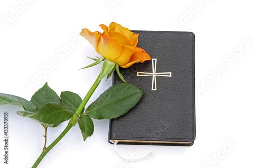 Valokuva  Gesangbuch mit orangegelber Rose vor weißem Hintergrund