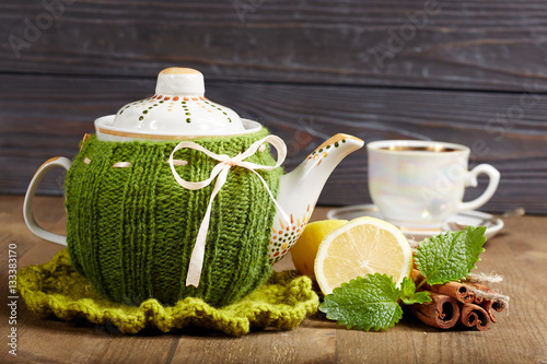 Staande foto Thee Teapot with handmade knitted cover, lemon, cinnamon, mint