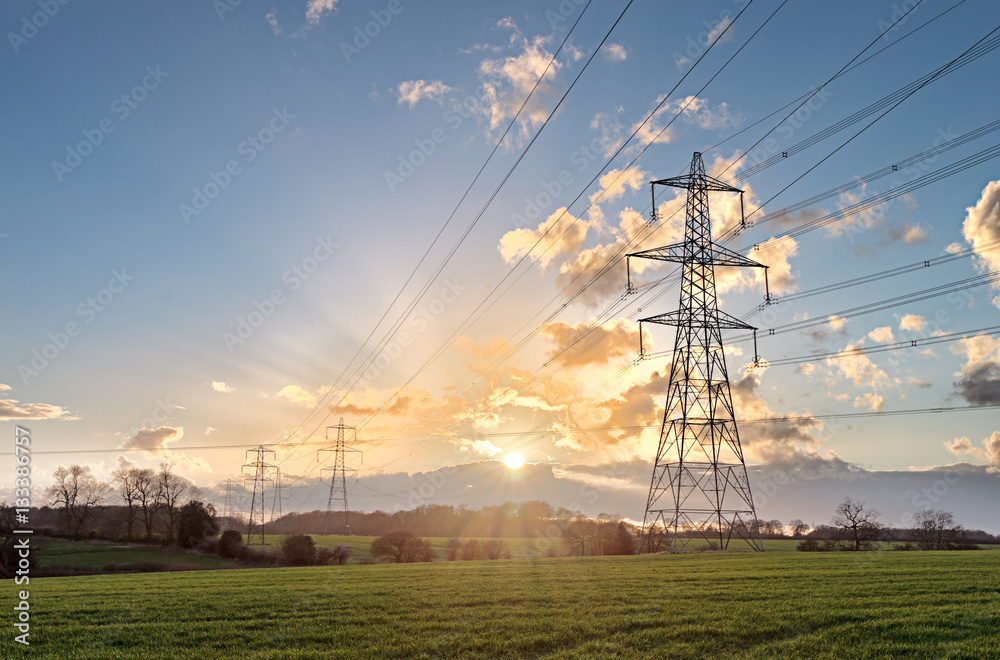 Fototapeta Electricity Pylon - UK standard overhead power line transmission tower at sunset.