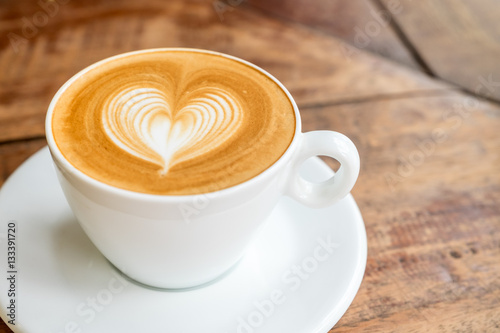 Fotografía Close up white coffee cup with heart shape latte art on wood tab