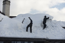 Men Clean The Roof From Snow