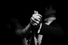 Couple Dancing On A Dark Background. Focus On Hands