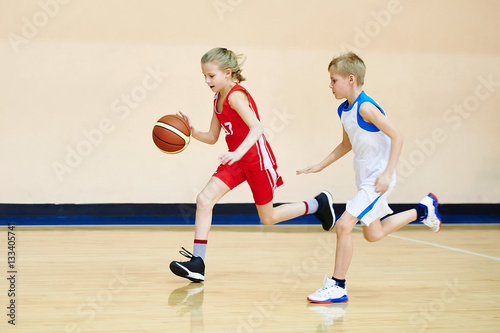 Girl and boy athlete in uniform playing basketball