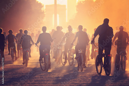 Poster Militaire Silhouettes of people on bicycles on the sunset in the city park