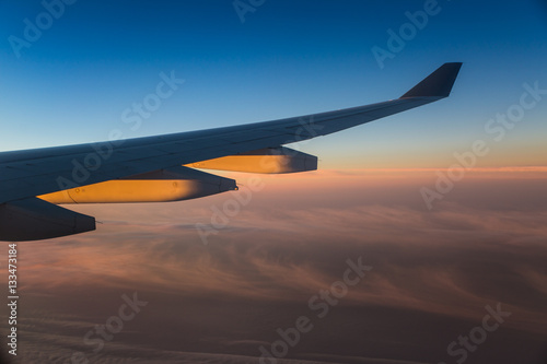 Fotografie, Obraz  Sunrise on the wing of a plane and clouds