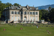 Historic manor house in Parc de la Grance overlooks a large lawn with visitors enjoying the summer day