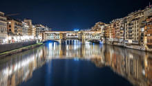 Ponte Vecchio At Night Is Reflected In The Arno River In Florence, Italy
