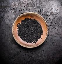 Black Cumin Seeds In Rustic Bowl On Dark Vintage Background, Top View. Nigella Sativa Seeds