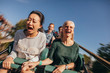 canvas print picture - Friends cheering and riding roller coaster at amusement park