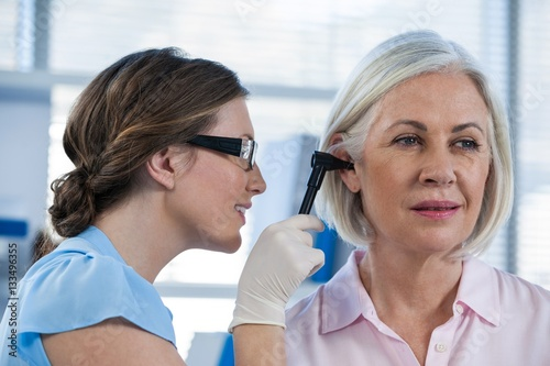 Photo Doctor examining patients ear with otoscope