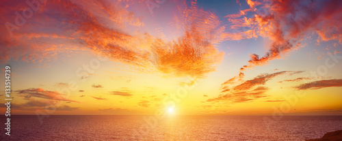 plakat Beautiful colorful sunset at the sea with dramatic clouds and sun shining. Beauty world natural outdoors travel background