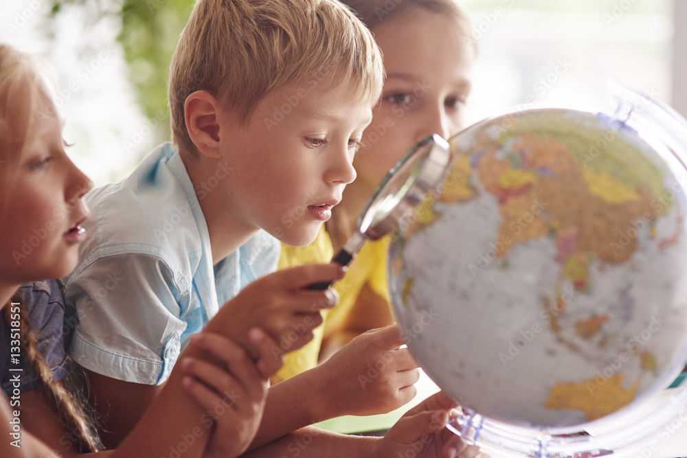 Fototapety, obrazy: Children using magnifying glass in Geography .
