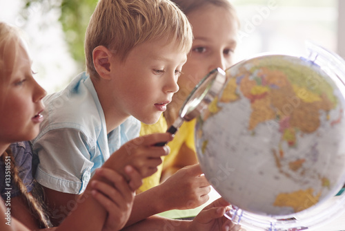 Fotografie, Tablou  Children using magnifying glass in Geography .