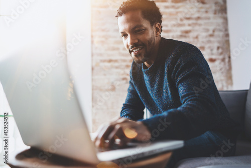 Cheerful African man using computer and smiling while sitting on the sofa.Concept of young business people working at home.Blurred background,flares.