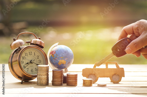 Fotografía  hand holding key of car with pile of money, alarm clock and globe on table, conc