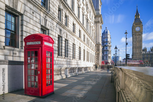 Foto op Canvas Londen rode bus London, England - Traditional red british telephone box with Big Ben and Double Decker bus at the background on a sunny afternoon with blue sky and clouds