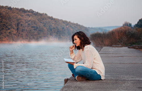 Thoughtful girl sitting by lake and writes diary