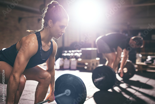 Poster Fitness Muscular man and woman lifting heavy barbells
