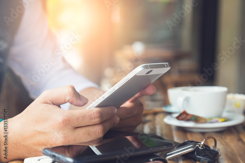 Photo  Young man using smartphone in coffee cafe, always connected concept