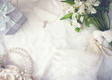 Arrangement Of Flower Bunch, Pearl Necklace, Gift Box, Bag, And Lace Glove On White Cloth Background, Romantic Concept, Frame, Copy Space